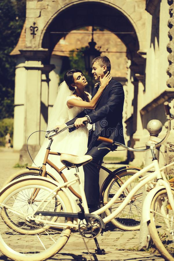 Bride holds groom on bicycle. Beautiful bride women holds elegant groom sitting on bicycle affectionate couple of newlyweds outdoors on sunny day stock photos