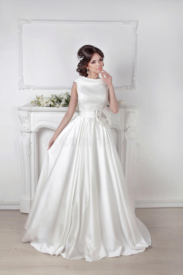 Beautiful bride woman posing in magnificent dress over white wall at modern interior stock photos