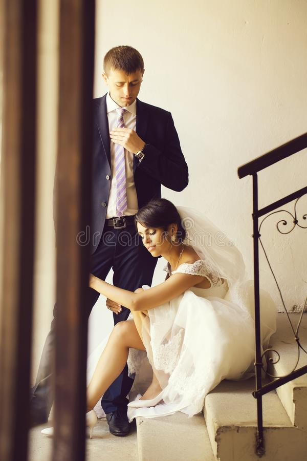 Bride holds leg of groom. Beautiful bride women in white wedding dress and veil sits on staircase and holds leg of elegant groom man stock photos
