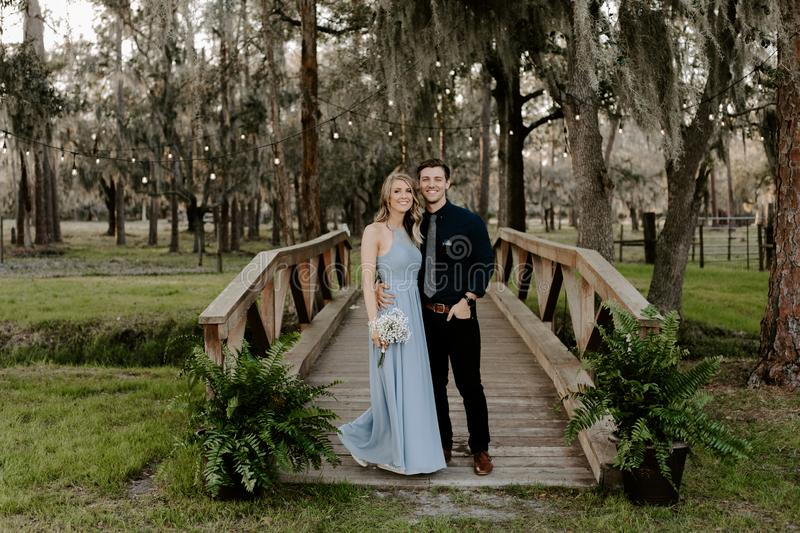 Beautiful Bridesmaid Woman in Blue Dress and Bouquet with Her Date at a Formal Wedding Party Celebration Event Outside in the Wood stock photo