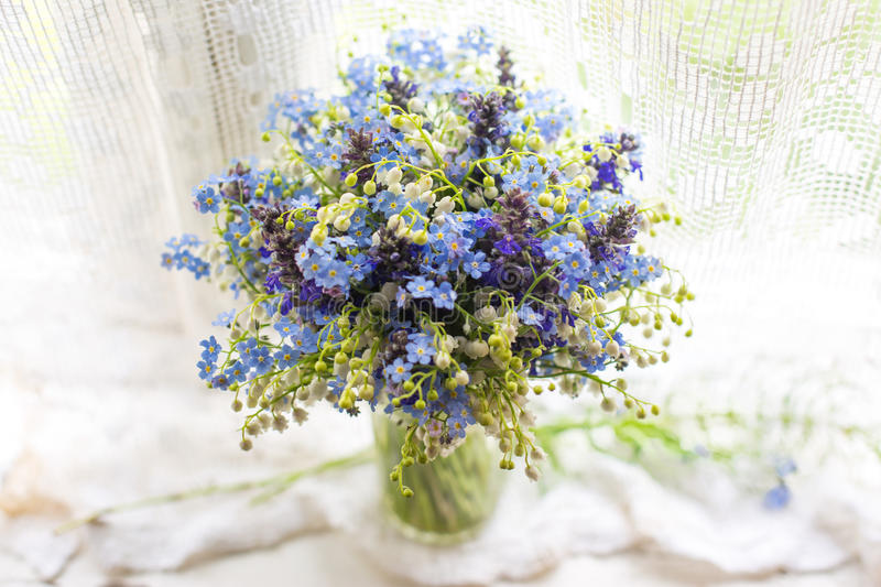 Beautiful bright blue and white bouquet with wild flowers on windowsill in sunlight . Closeup photo with bokeh royalty free stock photos