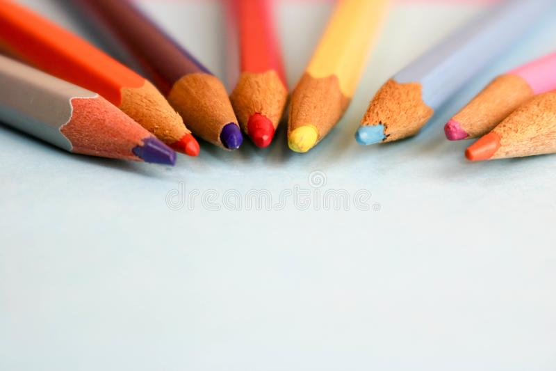 Beautiful bright colored wooden colored sharpening pencils for drawing. Flat lay and copy space on blue background stock image