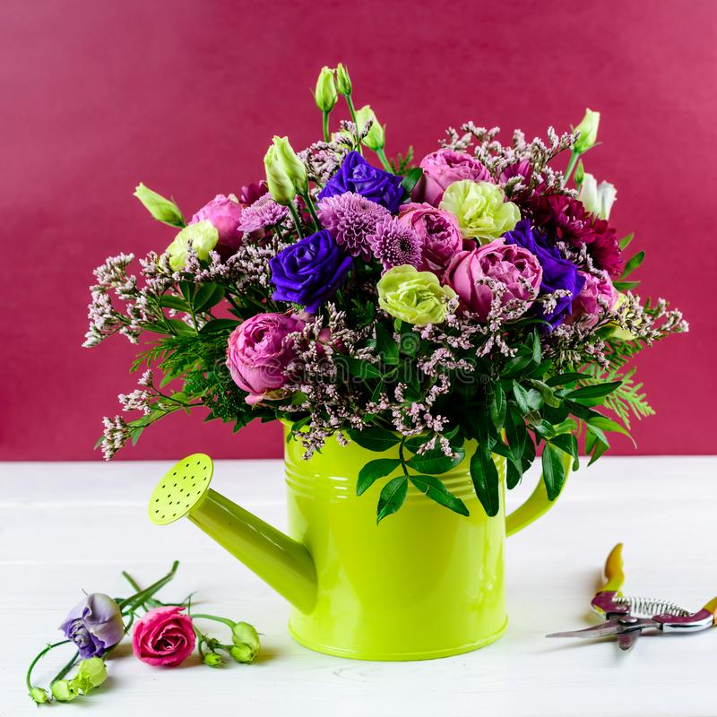 Beautiful bright creative bouquet with blue and pink roses, chrysanthemums in green watering can on red background. For 8 March stock photo