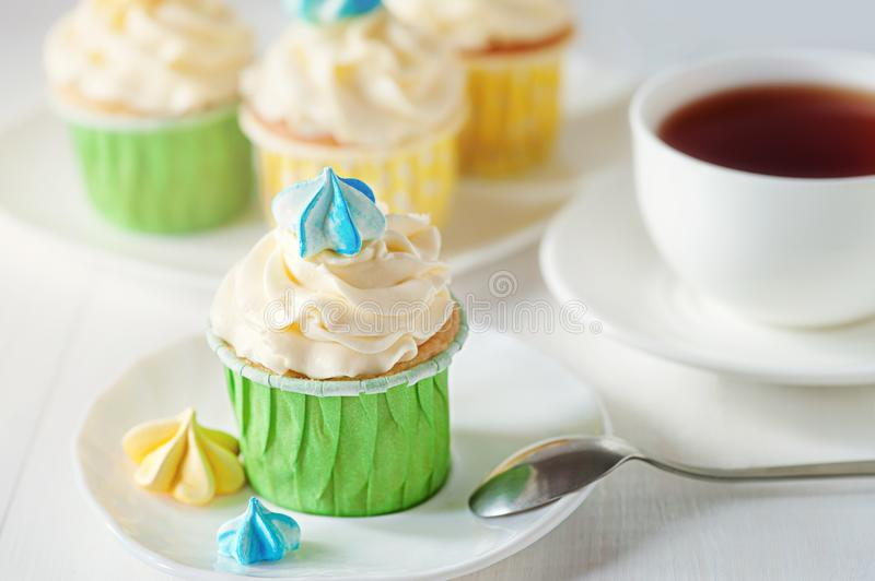 A beautiful bright ladies tea party with cup of tea cupcake with meringues stock images