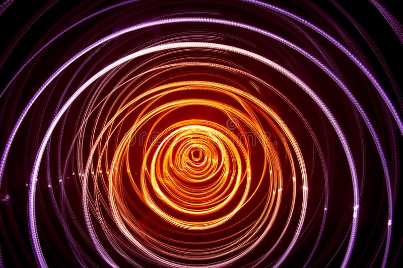 A beautiful, bright light swirl of colors. Futuristic light painting on a black background. Round light circles stock photo