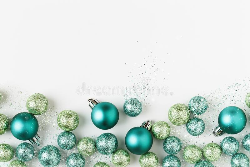 Beautiful, bright, modern Christmas holiday ornaments decorations in contemporary blue and green colors on white background. With sparkly luxe glitter special stock image