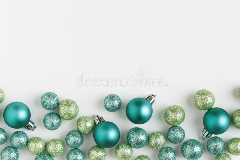 Beautiful, bright, modern Christmas holiday ornaments decorations horizontal border on white background. Contemporary blue and green colors with glitter balls stock photo