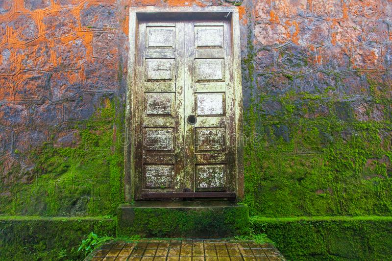 Beautiful bright orange and green moss on old stone wall and woo. Den door of the temple. Wat Sampov Pram, Preah Monivong Bokor National Park, Kampot, Cambodia stock image