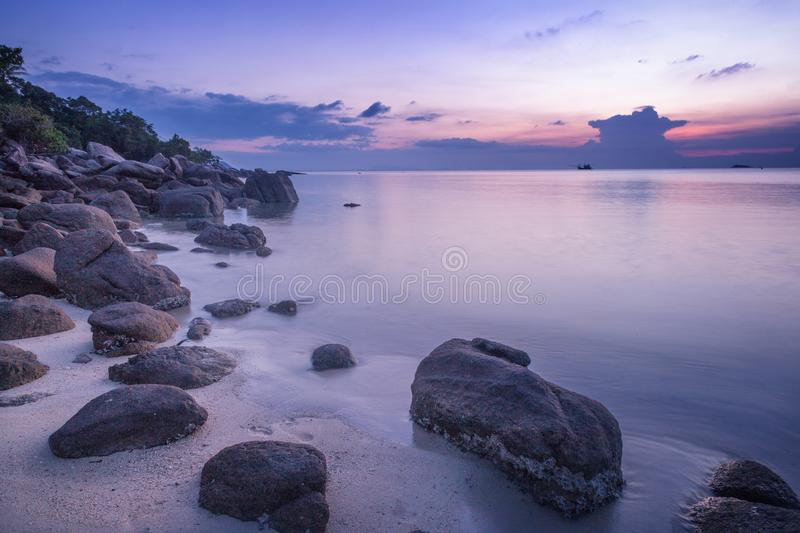 Beautiful bright purple pink sunset by the sea, stones on the sa stock photo