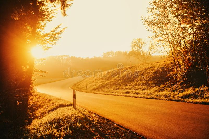 Beautiful sunset over small countryside road. Beautiful bright sunset over small countryside road royalty free stock images