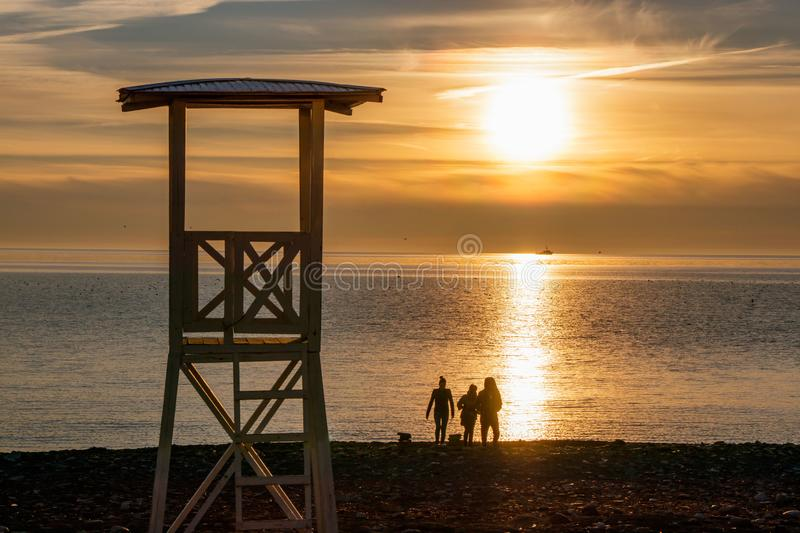 Beautiful and bright sunset on the sea coast in yellow tones. The silhouettes of three people and a tower for lifeguards stock photography