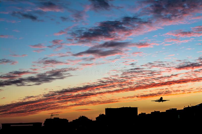 Beautiful bright sunset with the silhouette of a flying airplane. Over the city royalty free stock image