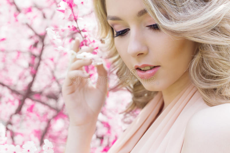 Beautiful bright young happy cute girl walks in the park near the pink flowering tree in a sunny day stock photo