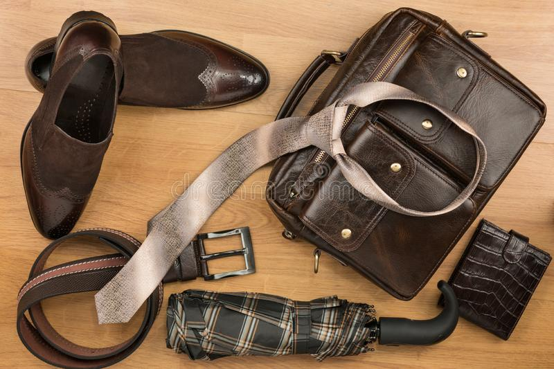 Beautiful brown classic men`s accessories, leather briefcase, belt, tie and shoes. Top view stock photo
