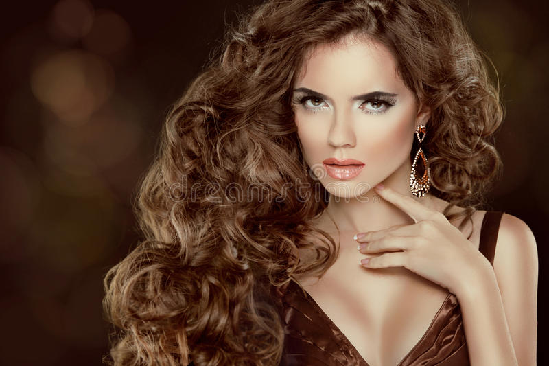 Beautiful brown hair, Fashion Woman Portrait. Beauty Model Girl. With luxurious wavy long hair isolated on dark background stock photo