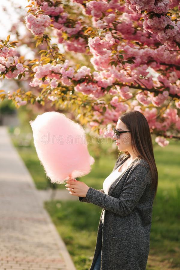 Beautiful brown hair model hold a cotton candy in hands and give a kiss. Young woman with pink cotton candy royalty free stock photography