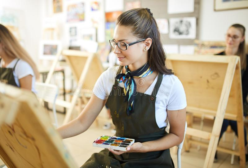 Beautiful brown-haired girl in glasses dressed in white t-shirt and brown apron with a scarf around her neck paints a. Picture at the easel in the art studio stock photography