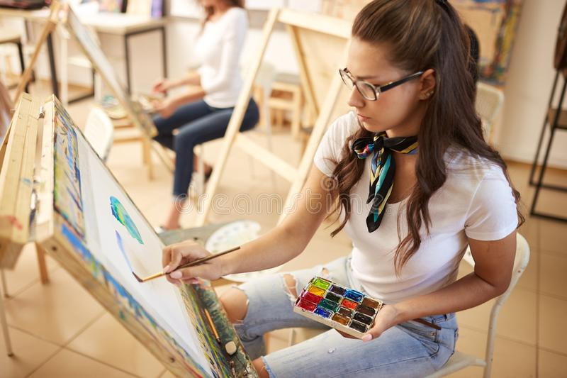 Beautiful brown-haired girl in glasses dressed in white t-shirt and jeans with a scarf around her neck paints a picture. In the art studio royalty free stock photos