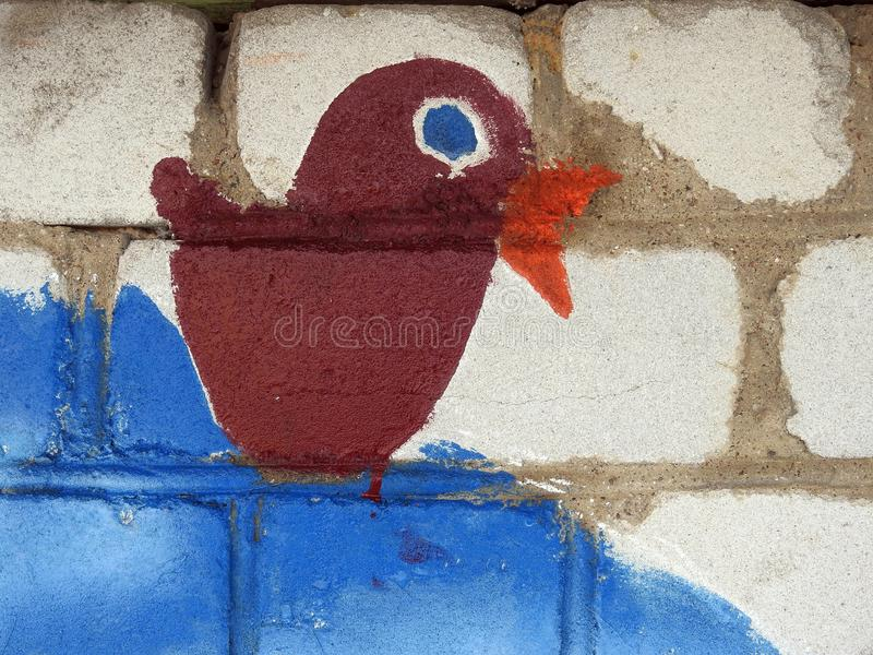 Pink bird painted on old wall, Lithuania. Beautiful brown painted bird on white bricks wall stock photos