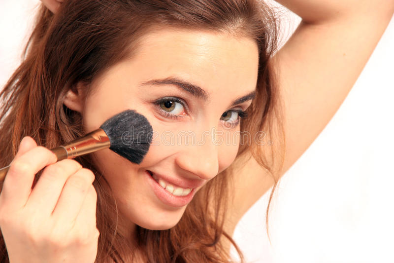 Beautiful brunet girl with make-up brush royalty free stock photography