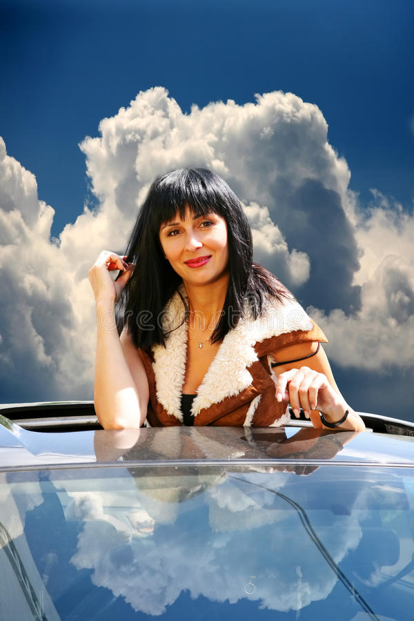 Beautiful brunette in the automobile royalty free stock photography