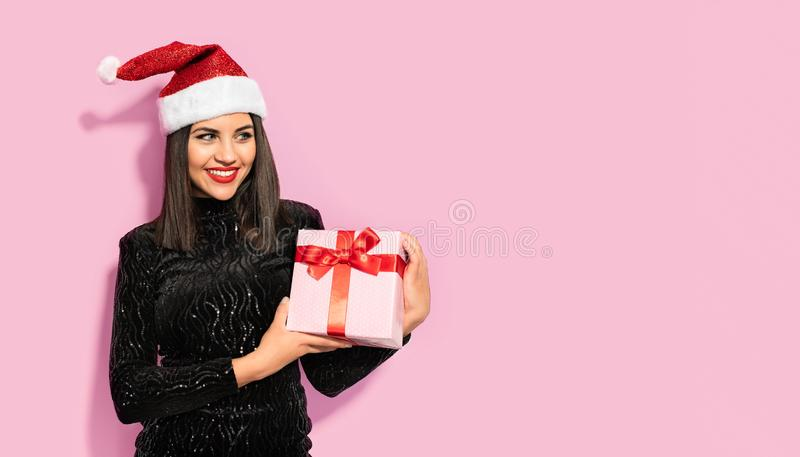 Beautiful Brunette in Black with Christmas Celebration Hat. Gift Concept royalty free stock photography