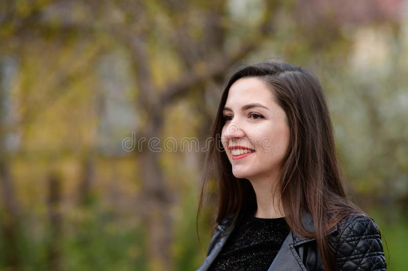 Beautiful brunette in a black jacket and red lips close-up. Closeup of street style fashion Portrait of a beautiful girl in autumn royalty free stock image
