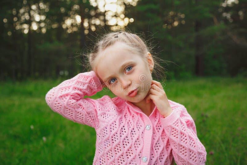 Beautiful brunette blue eyes little girl portrait on the park green grass royalty free stock photos