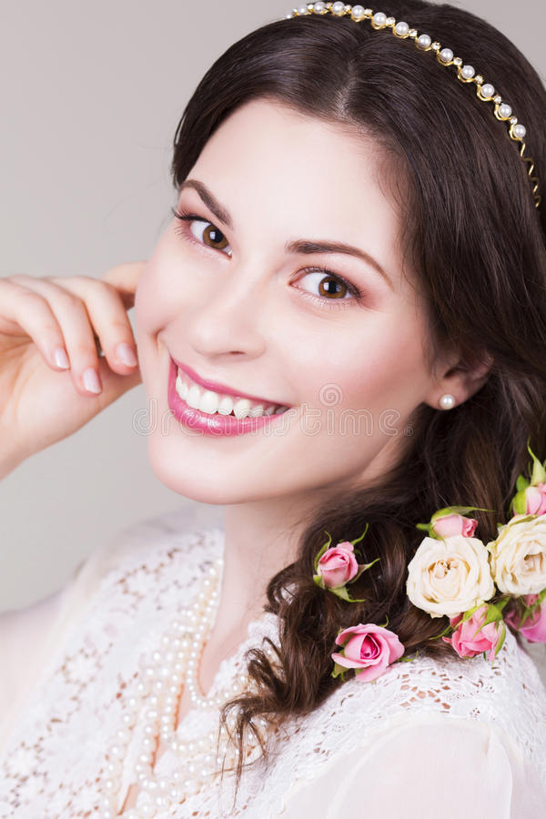 Beautiful brunette bride smiling with natural make up and flowers roses in her hairstyle. And looking sideways royalty free stock photos