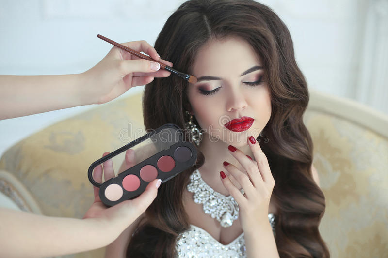 Beautiful brunette bride wedding portrait with makeup and hairstyle. Red lips and manicure nails. Stylist makes make-up model on royalty free stock photography