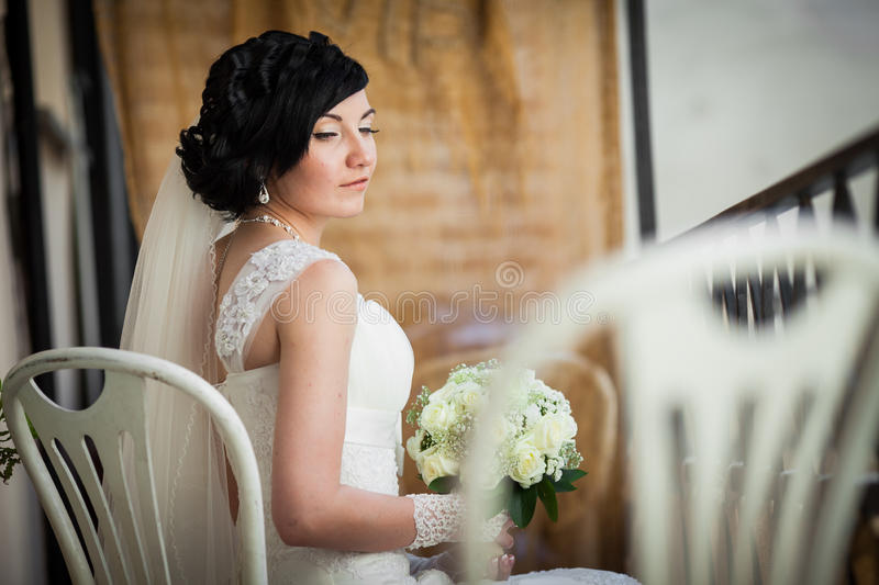 Beautiful brunette bride with white roses bouquet in elegant dress sitting on vintage white chair stock photos