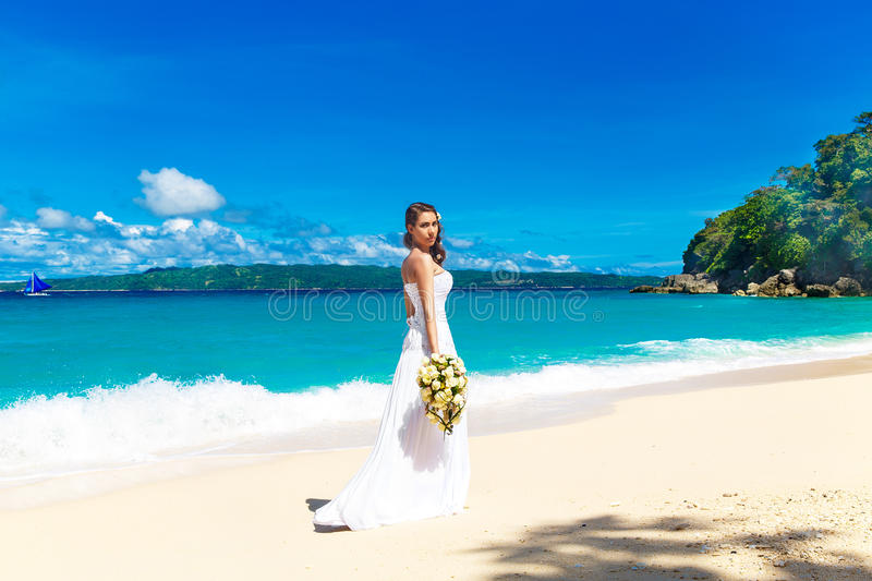 beautiful brunette bride in white wedding dress with big long white train and with wedding bouquet stand on shore sea royalty free stock photography