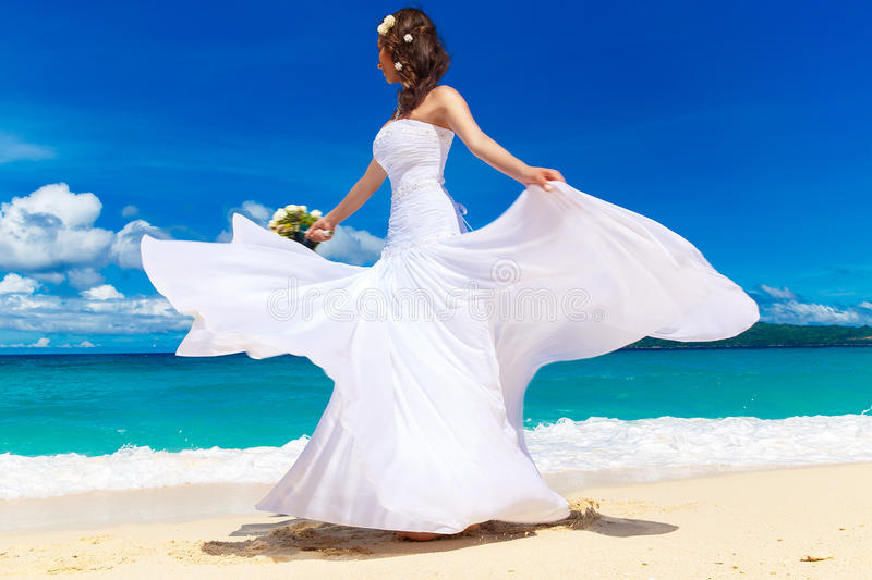Beautiful brunette bride in white wedding dress with big long white train and with wedding bouquet stand on shore sea. Tropical s. Ea in the background. Summer stock photography