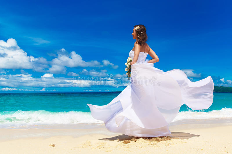 Beautiful brunette bride in white wedding dress with big long white train and with wedding bouquet stand on shore sea. Tropical s. Ea in the background. Summer stock images