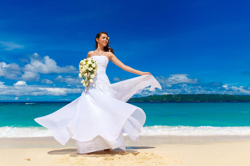 Beautiful brunette bride in white wedding dress with big long white train and with wedding bouquet stand on shore sea. Tropical s. Ea in the background. Summer royalty free stock photos