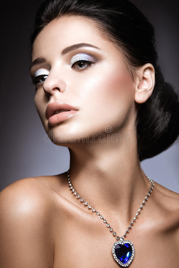 Beautiful brunette with a bright evening make-up with a necklace Heart of the Ocean. stock images