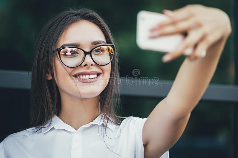 Beautiful brunette business woman photographing selfie on a phone in her hands outdoors royalty free stock images