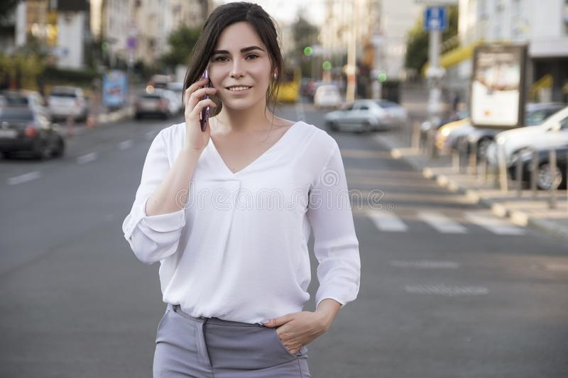 Beautiful brunette business woman in white skirt and grey suit trousers talking on a mobile phone in her hands outdoors. European royalty free stock photos