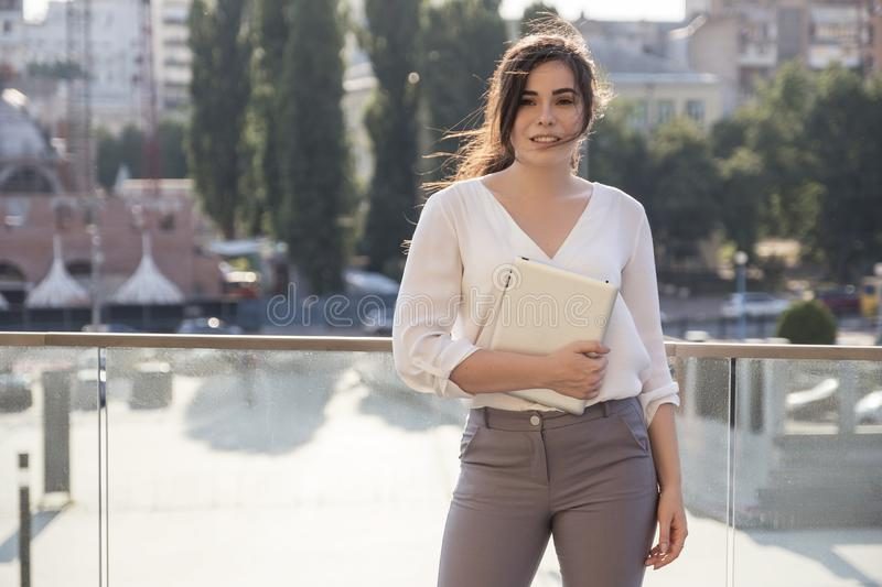 Beautiful brunette business woman in white skirt and grey suit trousers working on a tablet in her hands outdoors. European city. On background. copy space stock photo