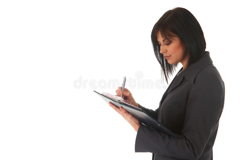 Beautiful brunette businesswoman. In business suit writing her appointments in diary on white background. Not isolated royalty free stock images