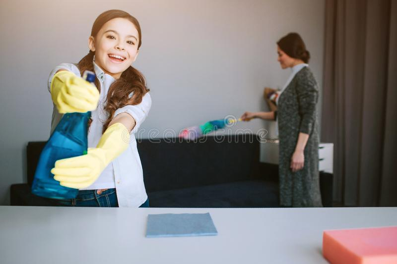Beautiful brunette caucasian mother and daughter cleaning together in room. Nice funny girl look on caera and use psray stock photos