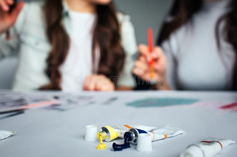 Beautiful brunette caucasian mother and daughter paint together in room. Blurred picture. Women painting at table. Tubes stock image