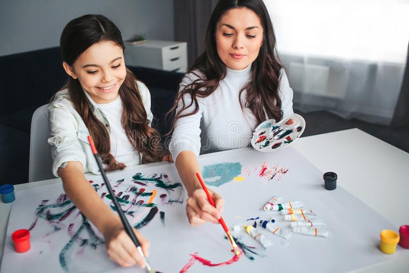 Beautiful brunette caucasian mother and daughter paint together in room. Happy girl hold brushes with mom. She smile stock image