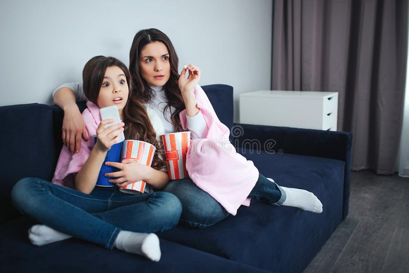 Beautiful brunette caucasian mother and daughter sit together in room. Scared adult and small women watch movie and eat. Popcorn. Frightened stock images