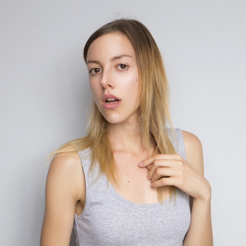 Beautiful brunette caucasian woman in grey blouse with bright em. Otions standing on a neutral grey background. Her hands make a gesture. She act sexy, seductive royalty free stock photos