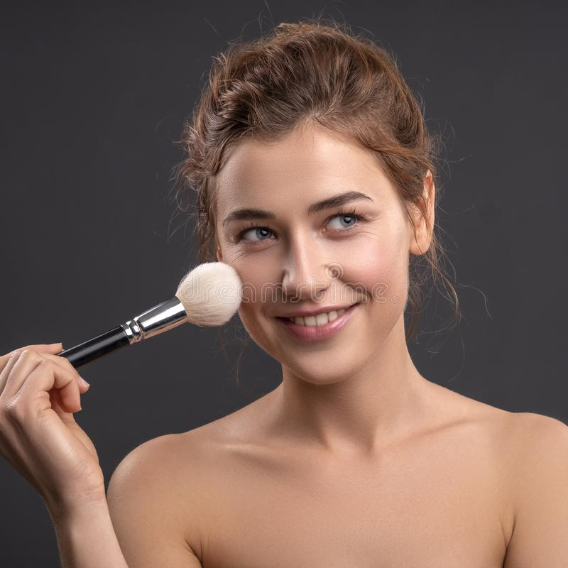 Beautiful brunette caucasian young woman prepare herself, applying powder on her cheeks with a brush. Clean, fresh, natural, flawl royalty free stock photo