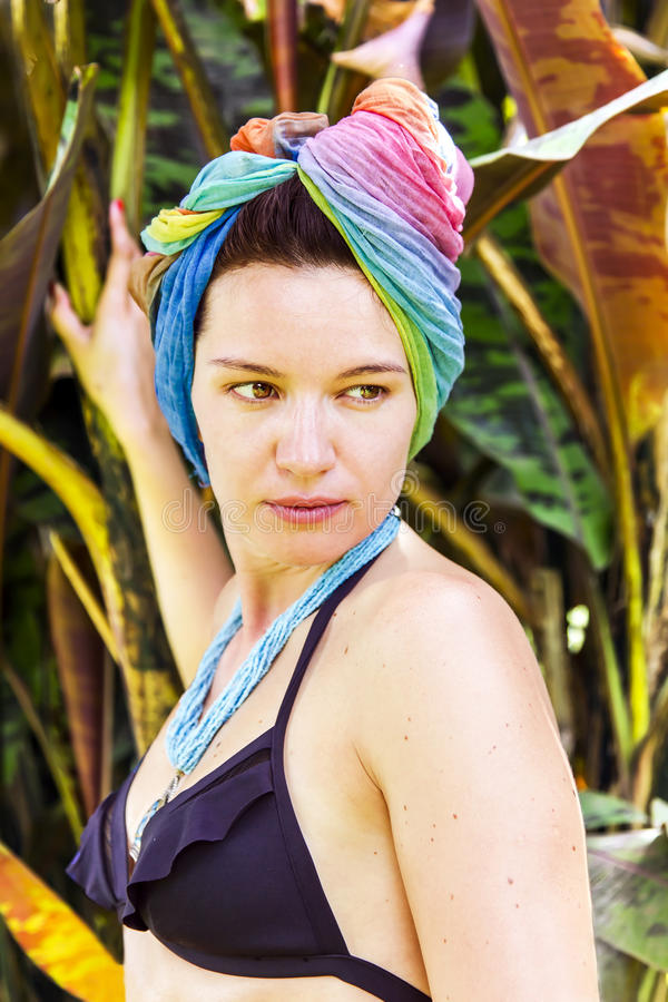 Beautiful brunette in a colored turban. And a bathing suit in a tropical garden, Arusha, Tanzania stock photos