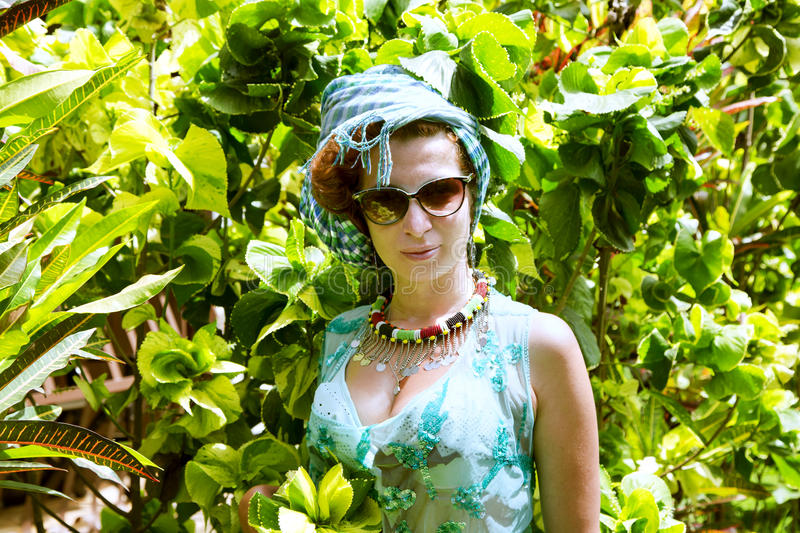 Beautiful brunette in a colored turban. And a bathing suit in a tropical garden, Arusha, Tanzania royalty free stock photos