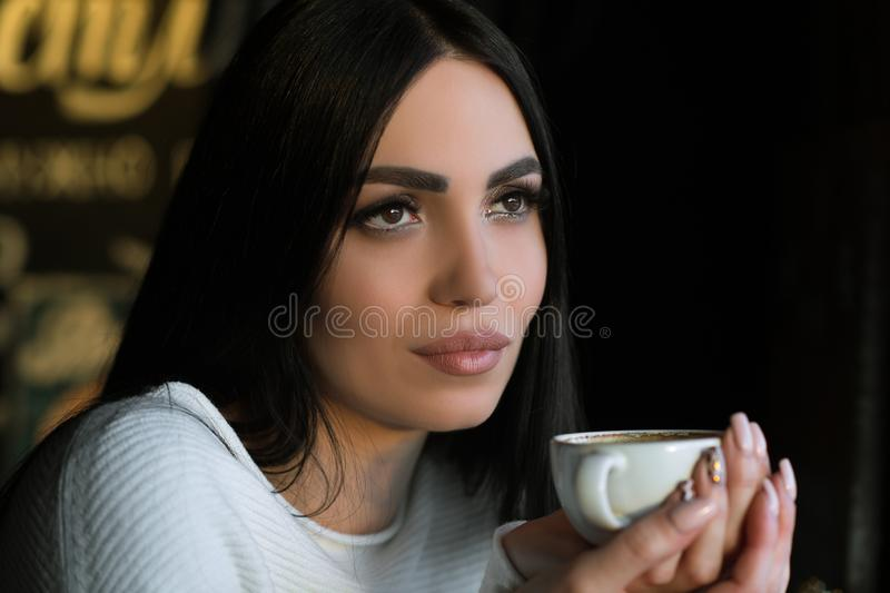 Beautiful brunette with cup of coffee in cafe royalty free stock photo