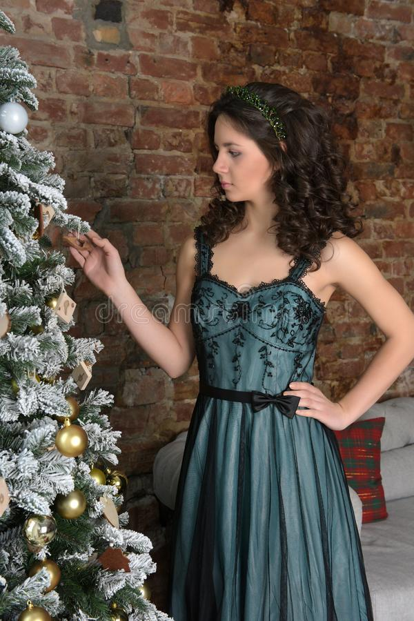 Beautiful brunette with curls in a green dress royalty free stock images